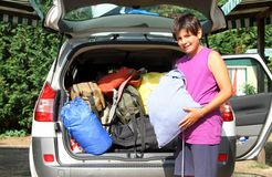Young boy with purple shirt car baggage charge before departure Stock Photography
