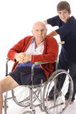 Young boy pushing great grandfather in wheelchair Stock Images