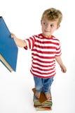 Young boy putting book on bookshelf Stock Photo