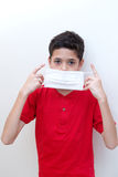 Young boy putting face mask on. Royalty Free Stock Images