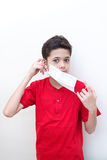 Young boy putting face mask on. Royalty Free Stock Photos