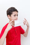Young boy putting on a face mask to stop spread of germs Stock Photos