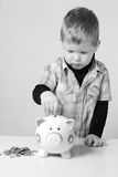 Young boy putting his savings to a piggy bank Stock Photography