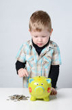 Young boy putting his savings to a piggy bank Royalty Free Stock Photos