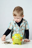 Young boy putting his savings to a piggy bank Stock Photo