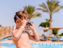 Young boy putting on his swimming goggles Royalty Free Stock Images