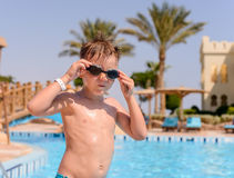Young boy putting on his swimming goggles Stock Photos