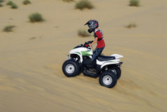Young boy quad biking in the dunes Royalty Free Stock Images