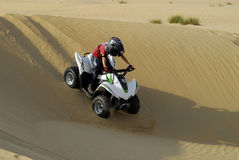 Young boy quad biking in the dunes. Young boy riding his quad bike in the desert Stock Photo