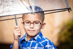 Young boy in the rain with umbrella royalty free stock photography