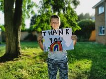 Young Boy with rainbow drawing and Thank You message for medical staff working through the Covid-19 Pandemic
