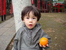 A young boy in raincoat with an orange in his hand Stock Photos