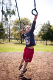 Young boy reaching on monkey bars Stock Photos