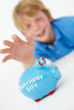 Young boy reaching for piggy bank Stock Images