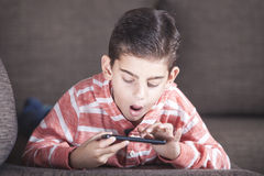 Young boy reacts while using his smart phone Royalty Free Stock Photo