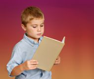 Young boy reading. A book against  background Stock Image