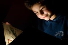 Young boy reading book stock photos