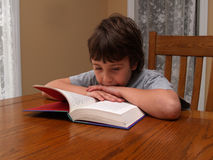 Young boy reading a book Stock Images