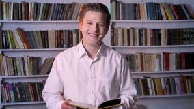 Young boy is reading book in library, watching at camera, smiling.  stock footage