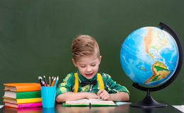 Young boy reading a book near empty green chalkboard.  Stock Photos
