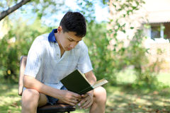 Young Boy Reading Book outdoors Royalty Free Stock Photo