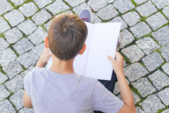 Young boy reading book outdoors Royalty Free Stock Images