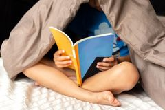 Young boy reading a book under the blanket in bed. royalty free stock images