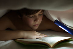 Young boy reading a book under the blanket or quilt Stock Image