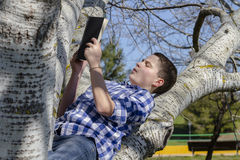 Young boy reading a book in the woods with shallow depth of fiel Stock Image