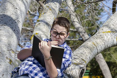 Young boy reading a book in the woods with shallow depth of fiel Stock Images