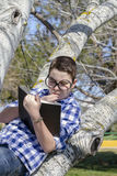 Young boy reading a book in the woods with shallow depth of fiel Royalty Free Stock Photos