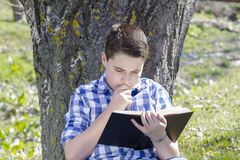 Young boy reading a book in the woods with shallow depth of fiel Stock Photo