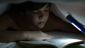 Young boy reading a captivating book at night stock video footage