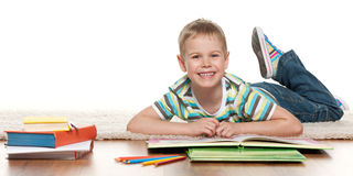 Young boy reading on the floor Royalty Free Stock Images