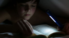 Young boy reading an interesting book at night stock video footage
