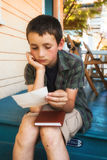 Young boy reading letter on front porch. Young boy in shorts reading letter on blue home steps Royalty Free Stock Photos
