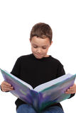 Young boy reading textbook Stock Photo