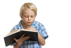 Young boy reading a thick book. Royalty Free Stock Photo