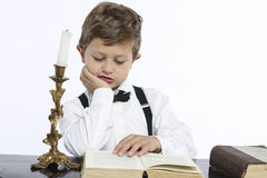 Young boy reads a big book Stock Photography