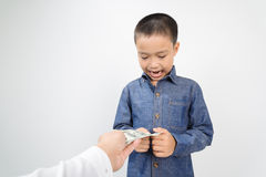 Young boy receive american bank note from hand Royalty Free Stock Image