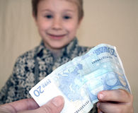 Young boy receiving money. A closeup of a young boy reaching out to receive some money and smiling as he does so Royalty Free Stock Photos
