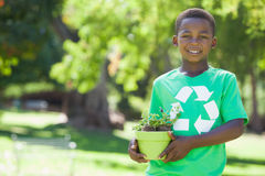 Young boy in recycling tshirt holding potted plant Royalty Free Stock Images