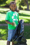 Young boy in recycling tshirt picking up trash Stock Images