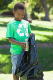 Young boy in recycling tshirt picking up trash Royalty Free Stock Photography