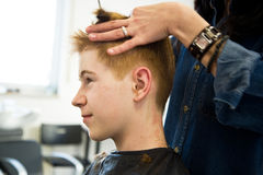 Young boy with red hair getting a haircut Stock Image