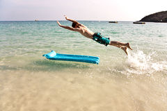 Young boy with red hair jumpy at the air matress. Boy with red hair is enjoying jumping on the air mattress at the crystal clear water at a beautiful fine sandy Royalty Free Stock Photography