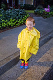 Young boy with red hair playing in the rain. Wearing yellow raincoat and rainboots Stock Photos