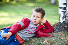 Young boy in red jacket resting on autumn grass in park Stock Images