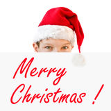 Young boy in red Santa hat hiding behind a paper Merry Christmas Stock Images