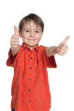 Young boy in the red shirt holds his thumbs up Royalty Free Stock Photo